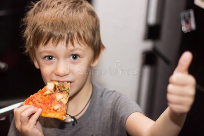 El muchacho come una pizza muy sabrosa con gran placer foto de archivo libre de regalías