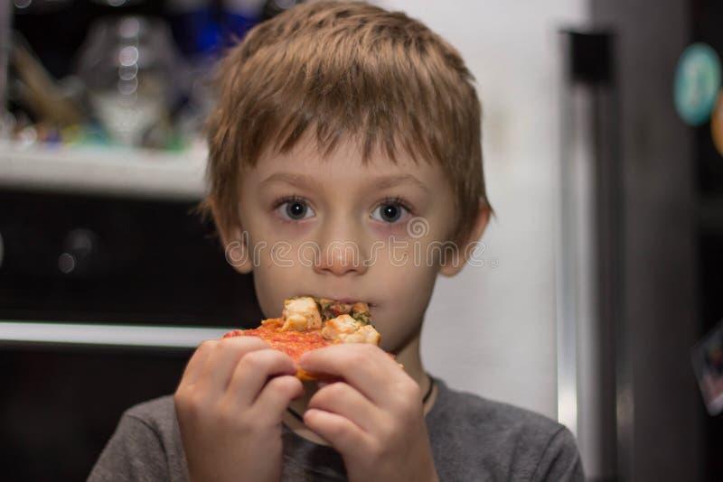 El muchacho come una pizza muy sabrosa con gran placer imagen de archivo