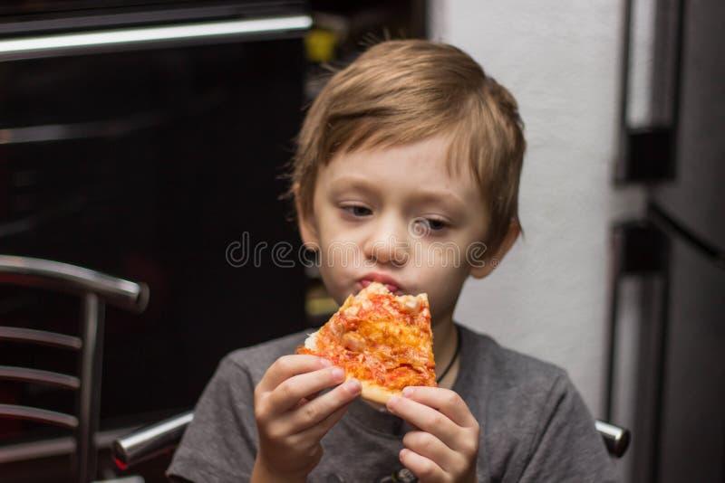 El muchacho come una pizza muy sabrosa con gran placer fotos de archivo