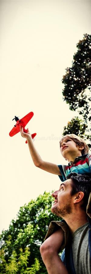 El muchacho con el avión del juguete que se sienta en padres lleva a hombros imagenes de archivo