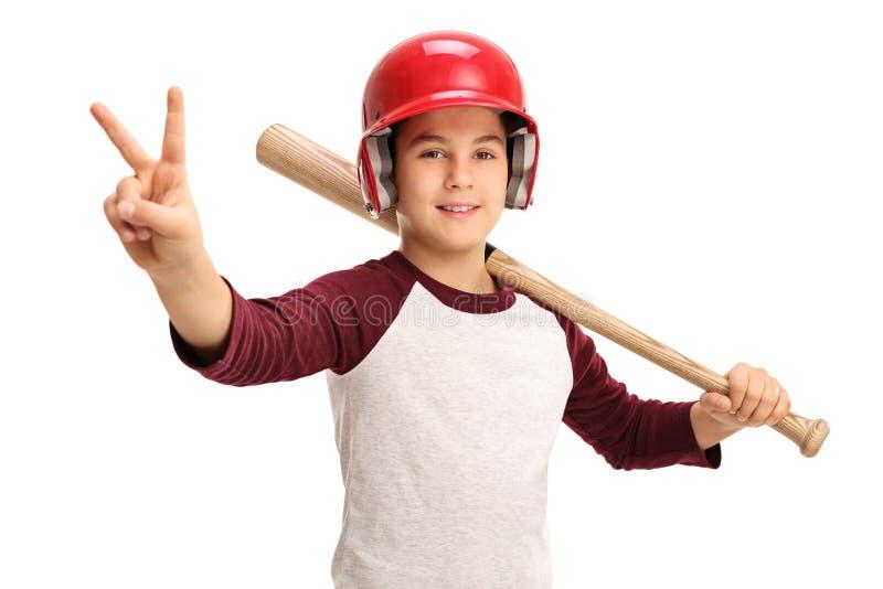 El muchacho con el bate de béisbol y el casco que hace la victoria firman fotografía de archivo
