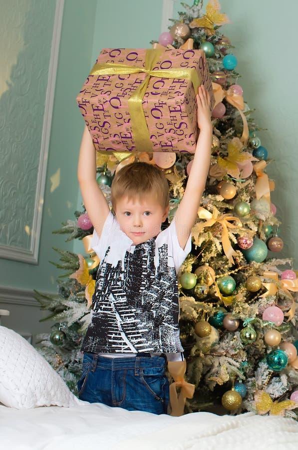 El muchacho con la caja de regalo en manos acerca al árbol imagenes de archivo