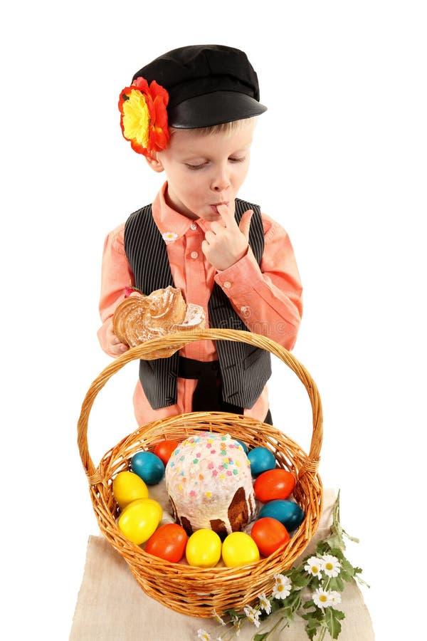 El muchacho con los huevos de Pascua y un día de fiesta se apelmazan foto de archivo
