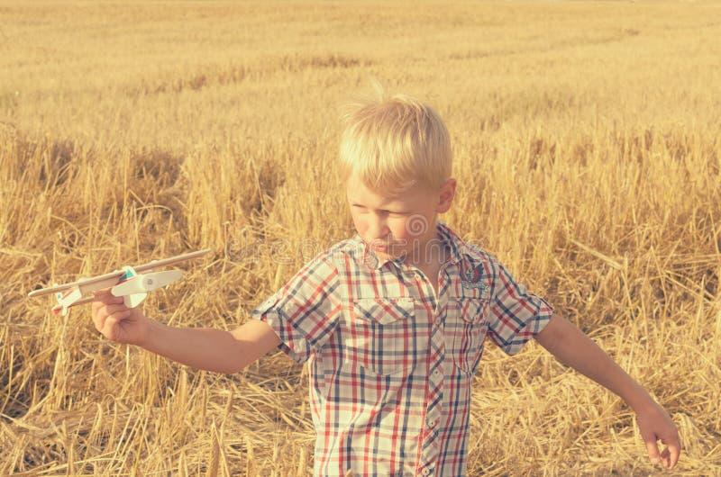 El muchacho con su mano funciona con el modelo del avión en el cielo fotografía de archivo