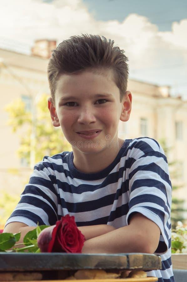 El muchacho con subió en una tabla en café de la calle foto de archivo