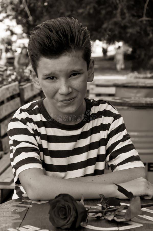 El muchacho con subió en una tabla en café de la calle fotografía de archivo libre de regalías