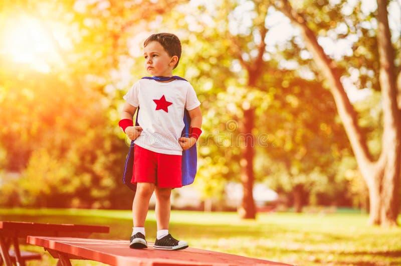 El muchacho confiado del pequeño niño juega al super héroe imagen de archivo