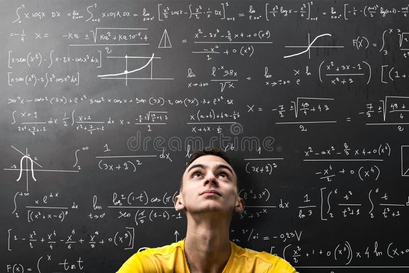 El muchacho considera aprensivo una fórmula matemática fotos de archivo
