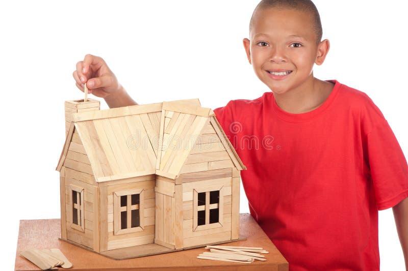 El muchacho construye la casa del popsicle imagenes de archivo