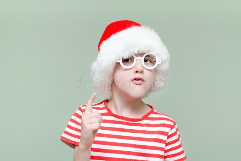 El muchacho contrariedad en sombrero y vidrios del ` s de Papá Noel amenaza con fing foto de archivo