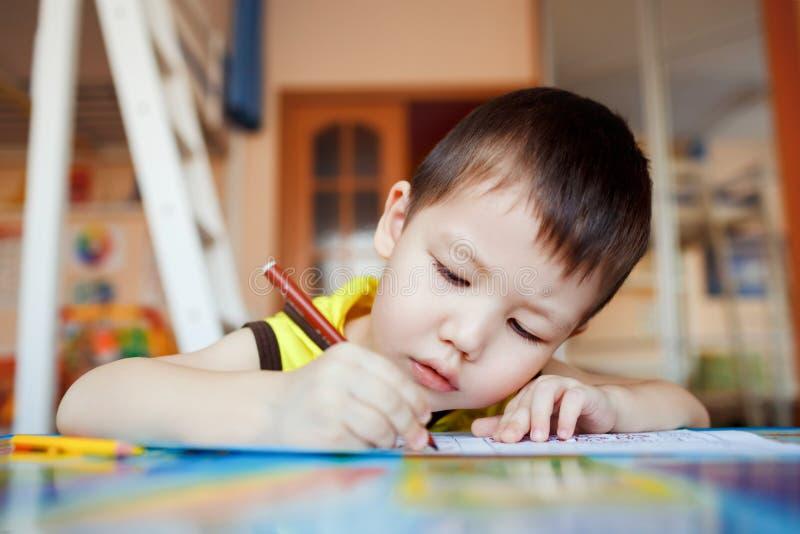 El muchacho cuidadosamente y dibuja atento en un special foto de archivo libre de regalías
