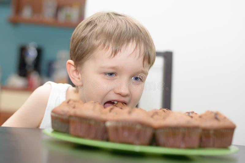 El muchacho de 4 años come la torta de chocolate imagen de archivo libre de regalías