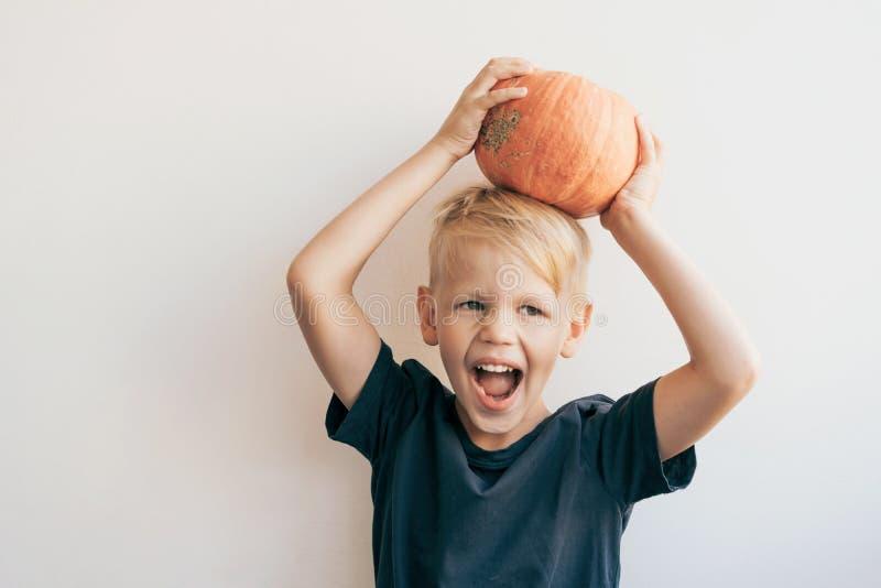 El muchacho de 5-7 años está engañando alrededor y pone una calabaza grande madura en su cabeza fotografía de archivo
