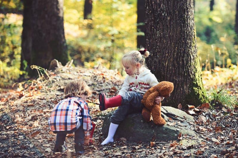 El muchacho de ayuda puso botas rojas en pies de la muchacha Concepto de la mano amiga fotografía de archivo