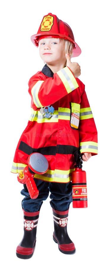 El muchacho de cuatro años vestido como bombero muestra que todo está bien fotos de archivo