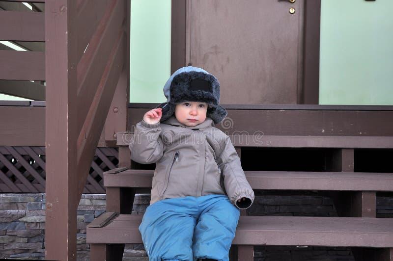 El muchacho de dos años en un casquillo con las oído-aletas se sienta en un pórtico imagen de archivo