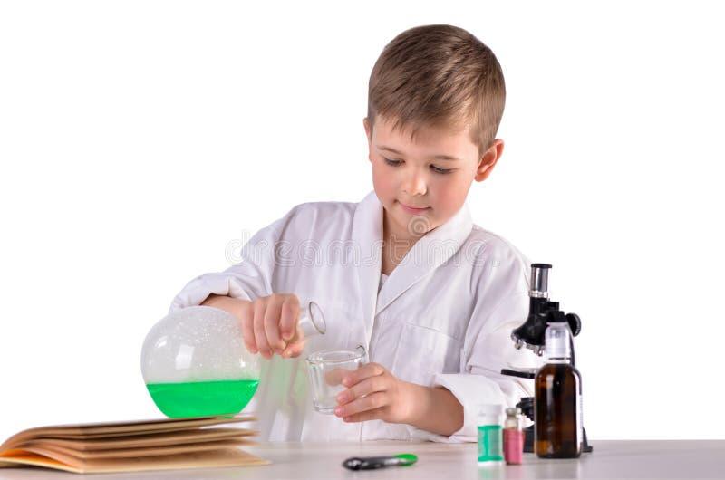 El muchacho de la ciencia vierte el líquido verde del frasco en el vidrio fotografía de archivo libre de regalías
