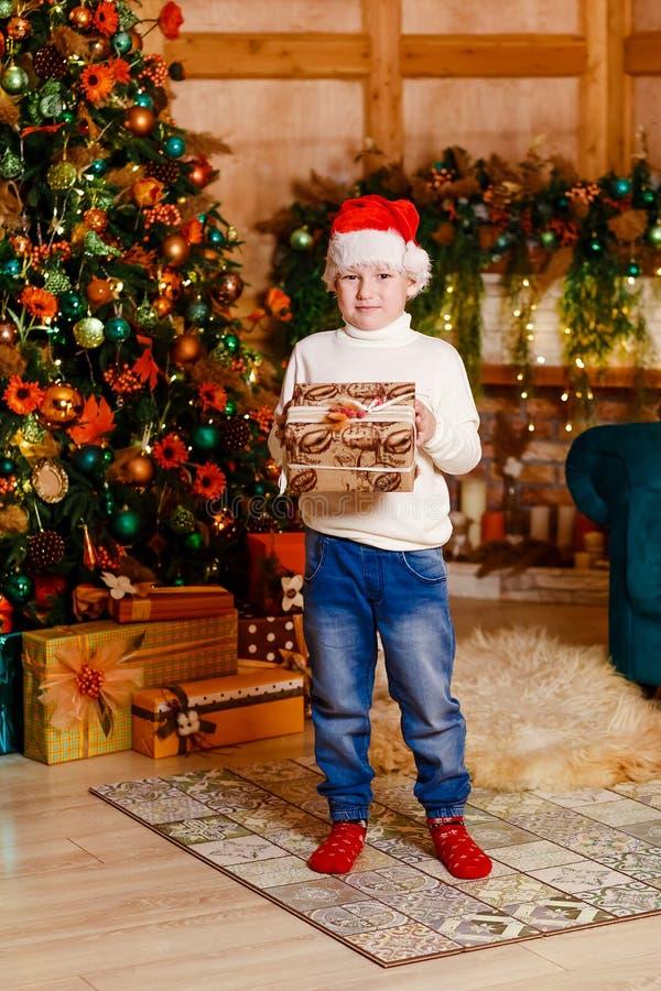 El muchacho de siete años en el casquillo y los vaqueros de Papá Noel en crecimiento completo con un regalo en sus manos se coloc imagen de archivo libre de regalías