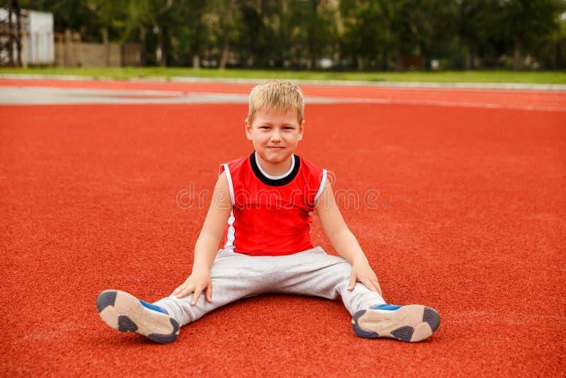 El muchacho de siete años en un uniforme de los deportes se sienta en la superficie roja del estadio fotografía de archivo libre de regalías