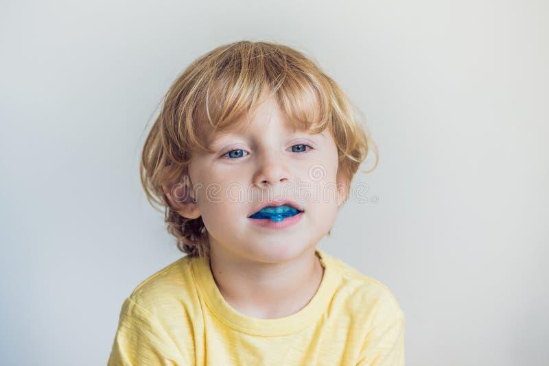 El muchacho de tres años muestra al instructor miofuncional para iluminar el mou imagen de archivo libre de regalías