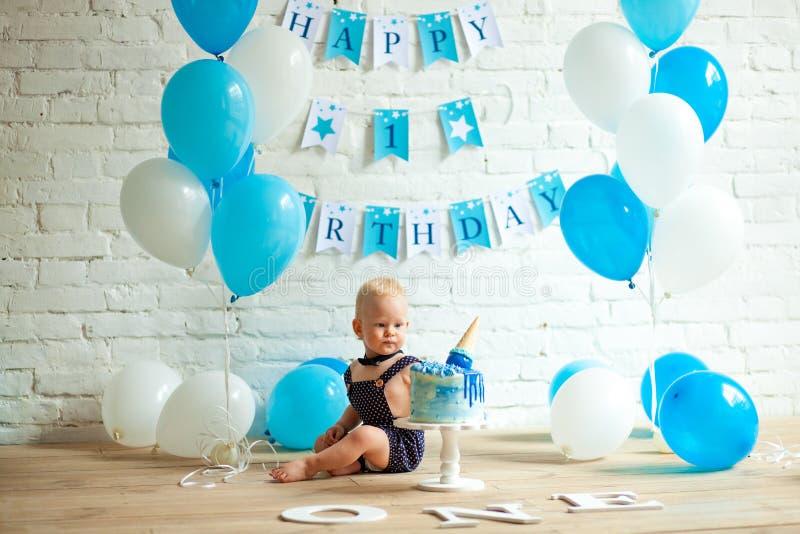El muchacho de un año está celebrando su primer cumpleaños entre los globos y la torta festiva imagen de archivo