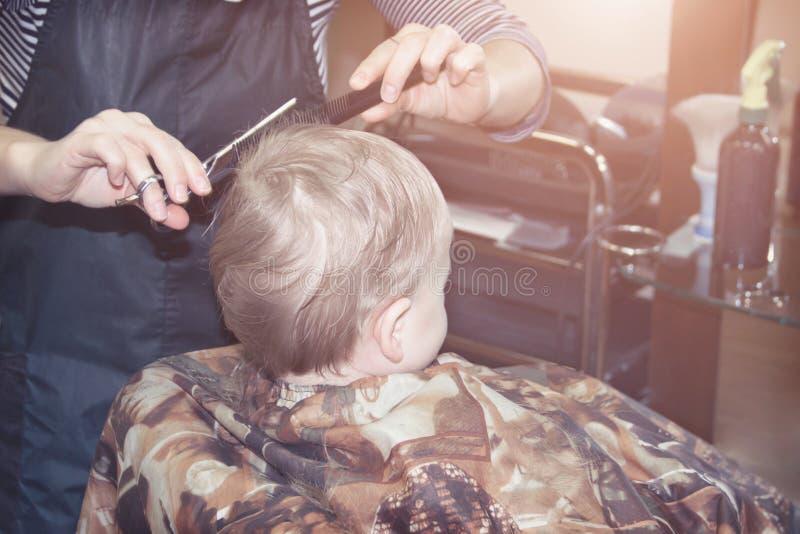 El muchacho de un año hace por primera vez el corte de pelo en una peluquería de caballeros imágenes de archivo libres de regalías