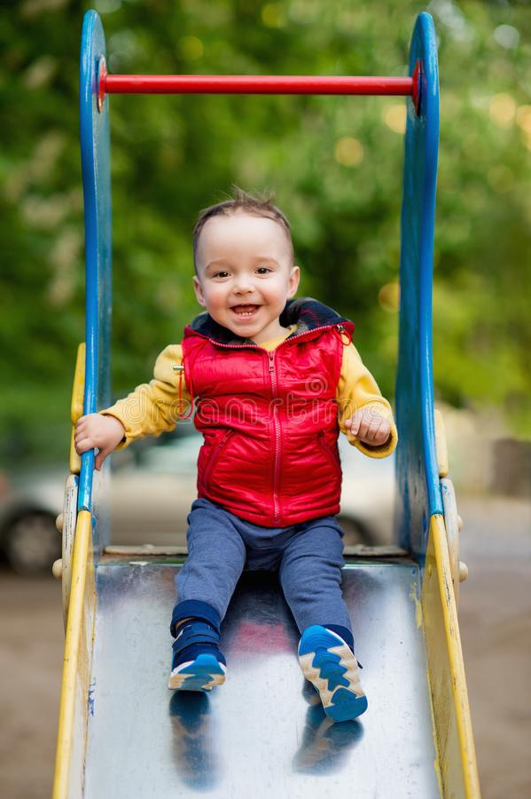 El muchacho de un a?o juega en un patio al lado de una diapositiva fotos de archivo