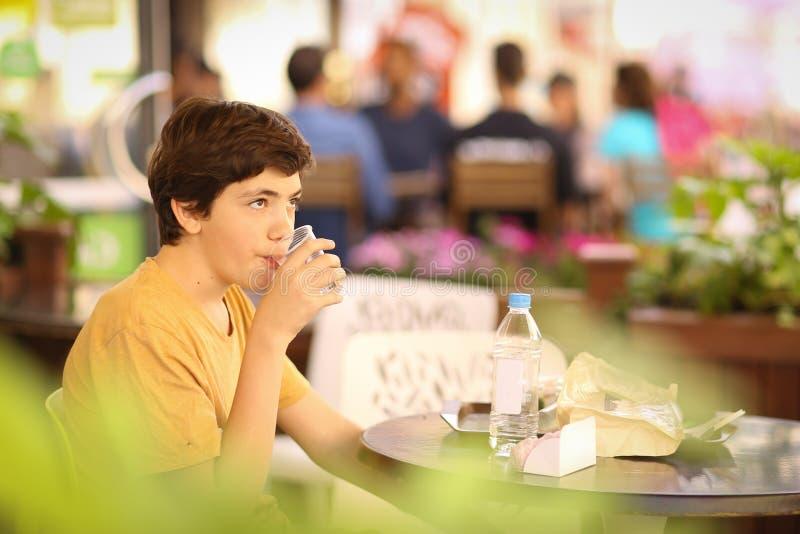 El muchacho del adolescente en hora de la almuerzo se sienta en café al aire libre del verano foto de archivo libre de regalías