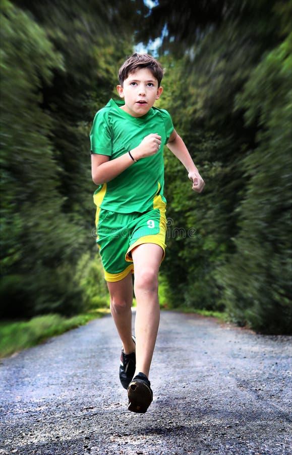El muchacho del adolescente en ropa de deportes corre en la carretera nacional foto de archivo libre de regalías