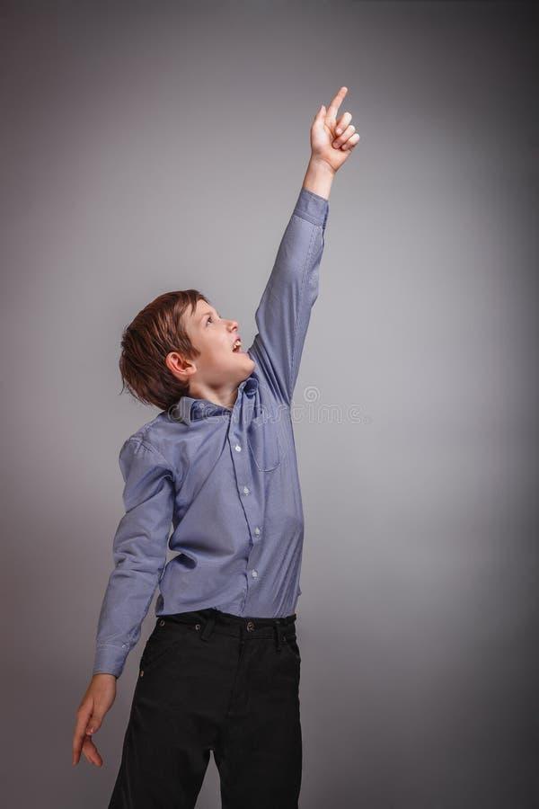 El muchacho del adolescente muestra la mano para arriba que ríe imágenes de archivo libres de regalías