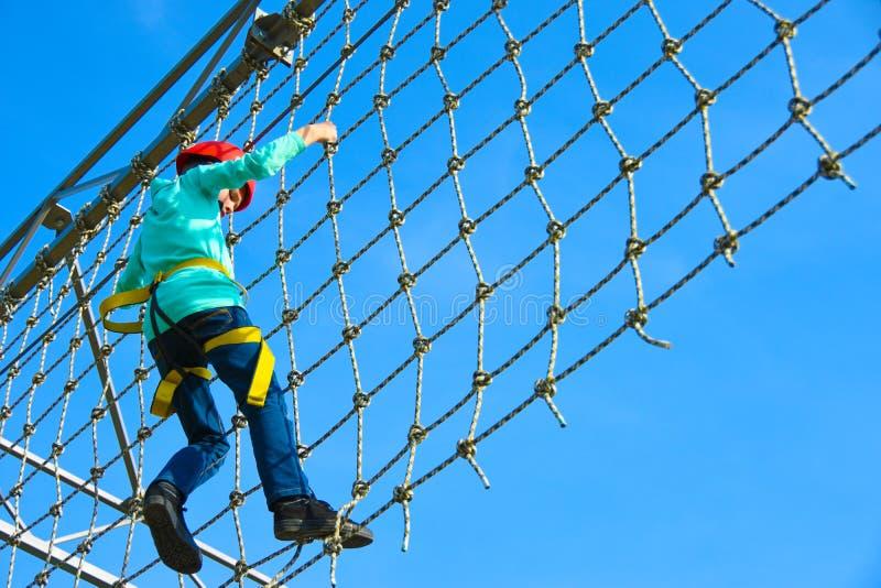 El muchacho del adolescente mueve la rejilla vertical en la carrera de obstáculos en el parque de atracciones, actividades al air imagen de archivo libre de regalías