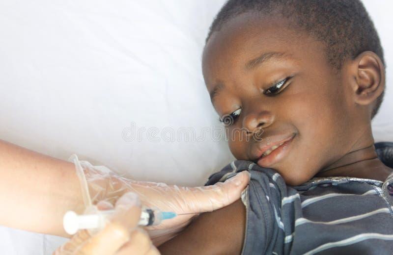 El muchacho del africano negro consigue una inyección médica como proyecto de la atención sanitaria para África imágenes de archivo libres de regalías
