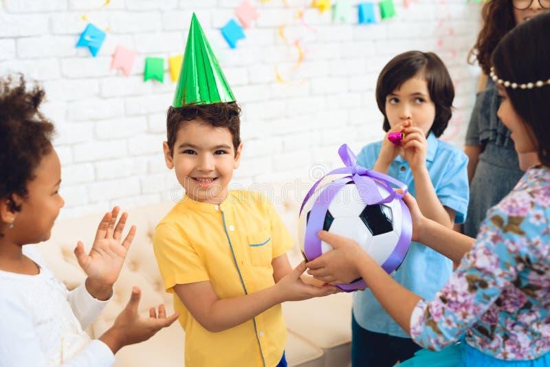 El muchacho del feliz cumpleaños recibe la bola del fútbol como regalo de cumpleaños Partido del feliz cumpleaños foto de archivo