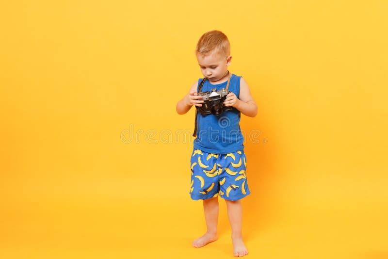 El muchacho del niño 3-4 años en ropa azul del verano de la playa sostiene la cámara retra aislada en fondo amarillo-naranja bril fotos de archivo libres de regalías