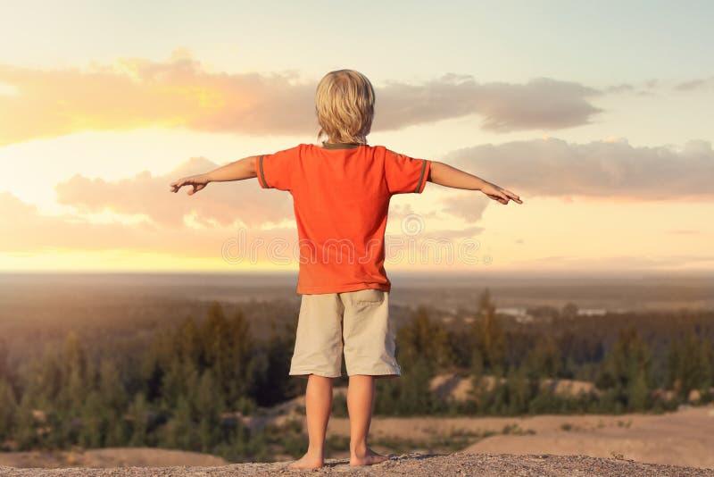 El muchacho del niño aumentó sus manos para arriba contra la puesta del sol del fondo fotografía de archivo libre de regalías