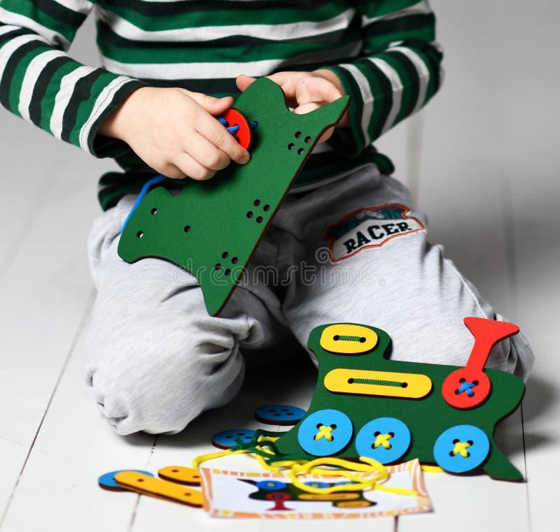 El muchacho del niño en jshirt azul claro con las rayas juega al juego educativo con el tren y los cordones coloridos de madera fotografía de archivo libre de regalías
