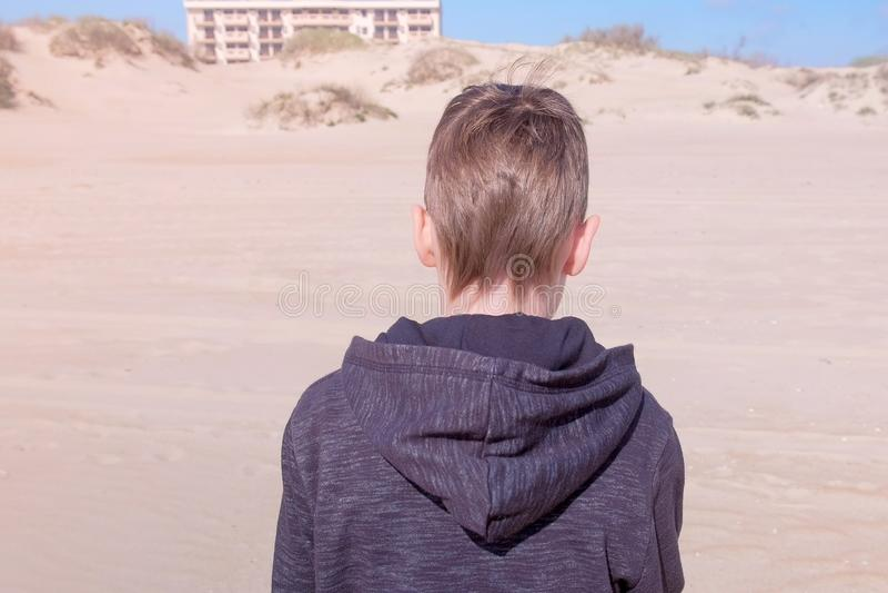 El muchacho del niño está caminando en la playa de la arena a las dunas de arena detrás ve actividades del aire libre fotografía de archivo