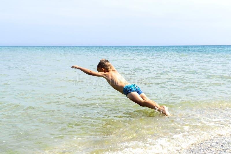 El muchacho del niño está saltando en el mar imagen de archivo