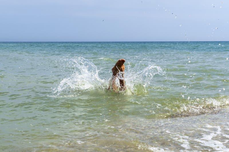 El muchacho del niño está saltando en el mar foto de archivo