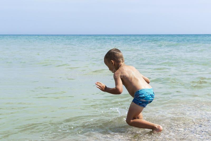El muchacho del niño está saltando en el mar imagen de archivo libre de regalías
