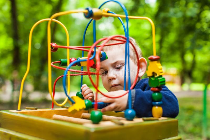 El muchacho del niño juega con un juguete lógico multicolor fotos de archivo libres de regalías