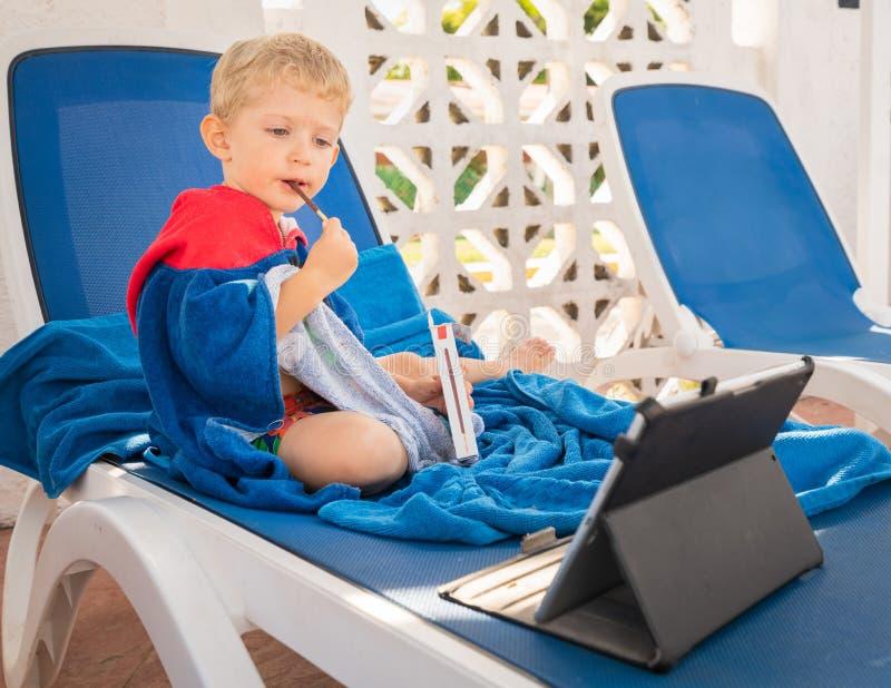 El muchacho del niño se está sentando en las sillas de playa y come y mira la tableta delante de él fotos de archivo libres de regalías
