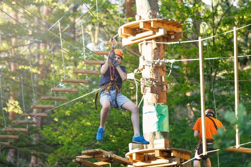 El muchacho deportivo, joven, lindo en la camiseta blanca pasa su tiempo en parque de la cuerda de la aventura en casco y el equi fotografía de archivo