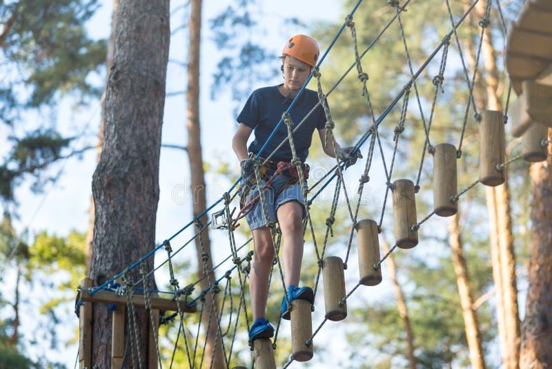 El muchacho deportivo, joven, lindo en la camiseta blanca pasa su tiempo en parque de la cuerda de la aventura en casco y el equi imágenes de archivo libres de regalías
