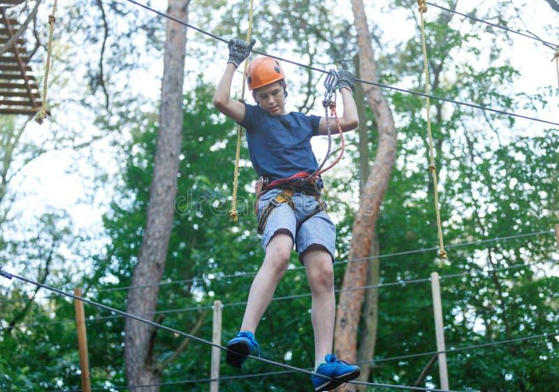 El muchacho deportivo, joven, lindo en la camiseta blanca pasa su tiempo en parque de la cuerda de la aventura en casco y el equi foto de archivo