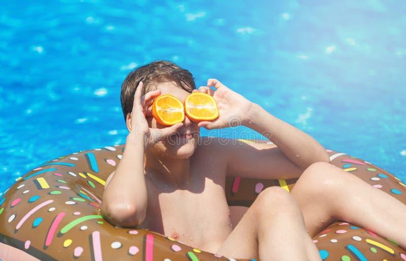 El muchacho deportivo lindo nada en la piscina con el anillo del buñuelo y se divierte, sonrisas, naranjas de los controles vacac foto de archivo libre de regalías
