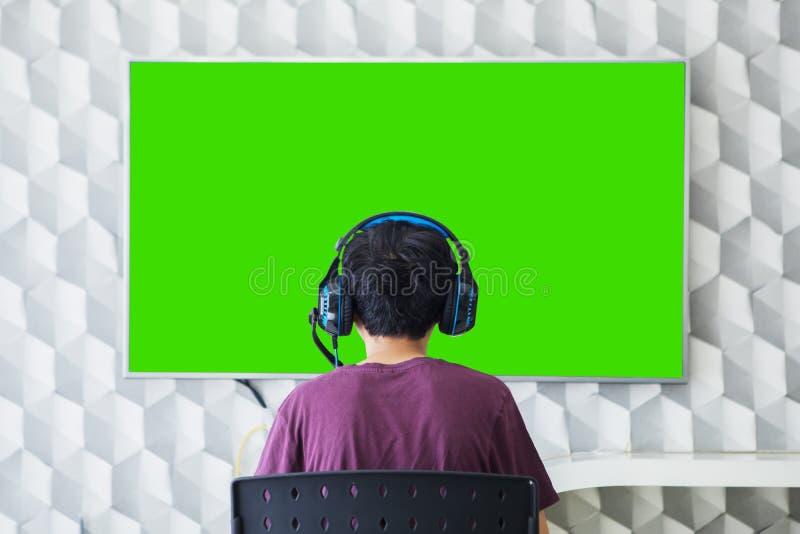El muchacho desconocido del preadolescente ve la TV con el auricular fotografía de archivo