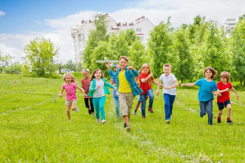 El muchacho detiene el juguete y a niños blancos grandes del aeroplano detrás imágenes de archivo libres de regalías