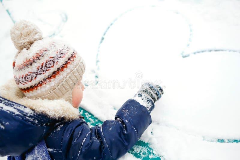 El muchacho dibuja el corazón en nieve outdoor Invierno, amor, amistad, concepto fotos de archivo libres de regalías