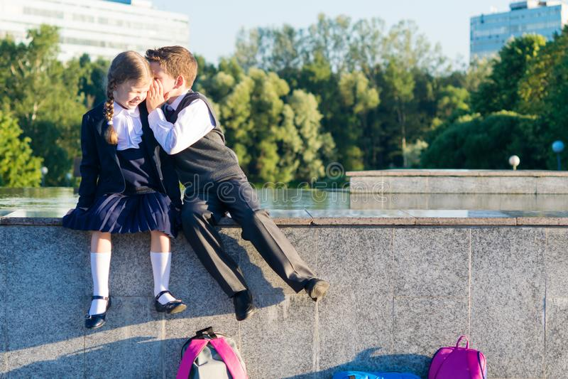 El muchacho dice a muchachas los secretos de la escuela, niños en la ropa para la escuela imágenes de archivo libres de regalías